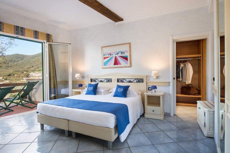 HOTEL HERMITAGE ISOLA D'ELBA le camere con vista giardino mediterraneo sono arredate con con mobili in legno chiaro